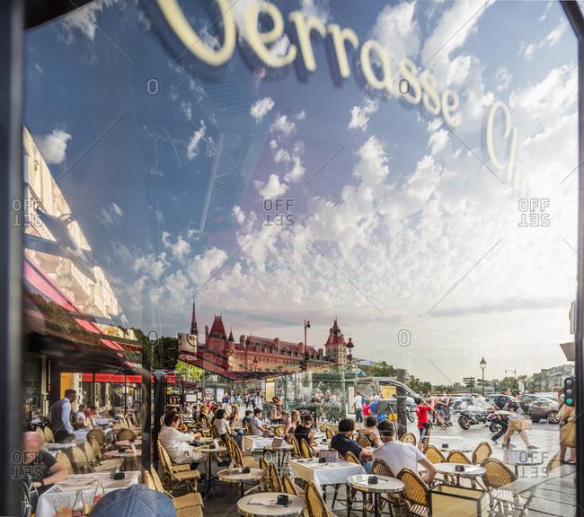 Paris, France - June 22, 2017: Place (square) Saint Michel, the covered terrace of Le Depart Saint Michel restaurant with the reflection of Palais de la Cite
