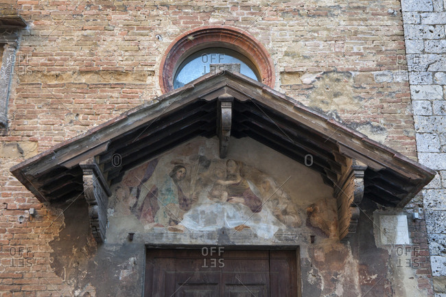 Siena, Italy - May 28, 2015: Weathered biblical artwork adorns the wall above a church door