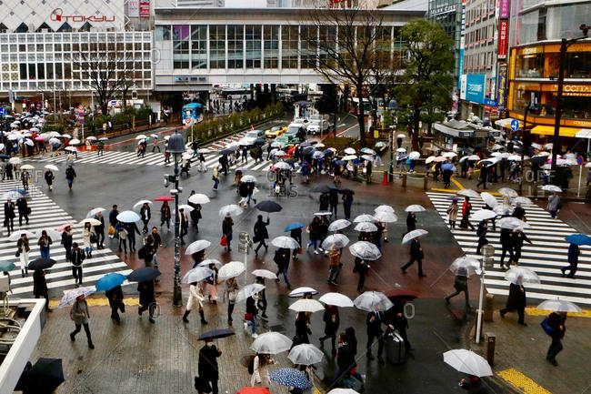 Tokyo, Japan - March 20, 2017: People walk across the Shibuya Crossing in the rain