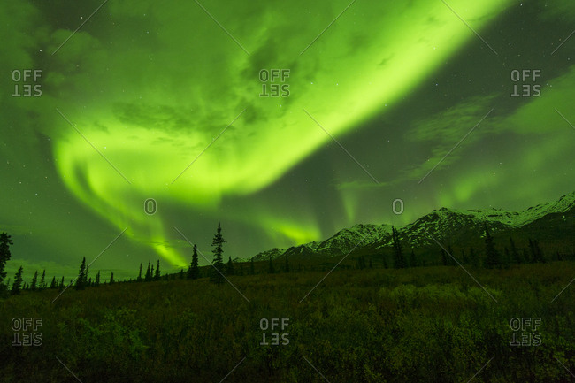 The northern lights swirl over the mountains