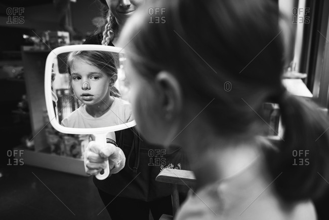 Girl looking at her pierced ears in her reflection in mirror