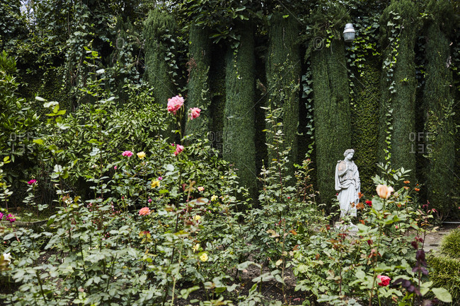 Los Angeles, California, USA - June 24, 2017: Statue in garden with rose bushes and greenery in the Holmby Hills neighborhood