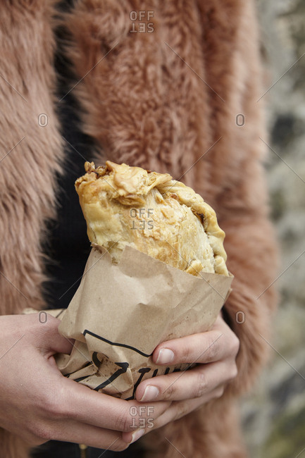 Cornish Pasty Pie held in brown paper packaging. Lifestyle street food image in a seaside town