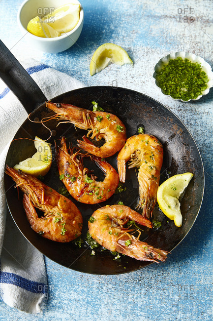 Tiger Prawns cooked in rustic frying pan with lemon wedges, coriander and olive oil photographed on blue background.