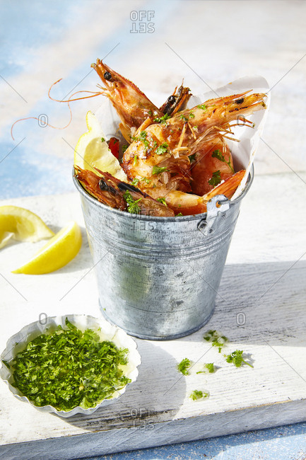 Grilled Tiger Prawns served in mini bucket garnished with parsley oil and lemon wedges on blue surface background.