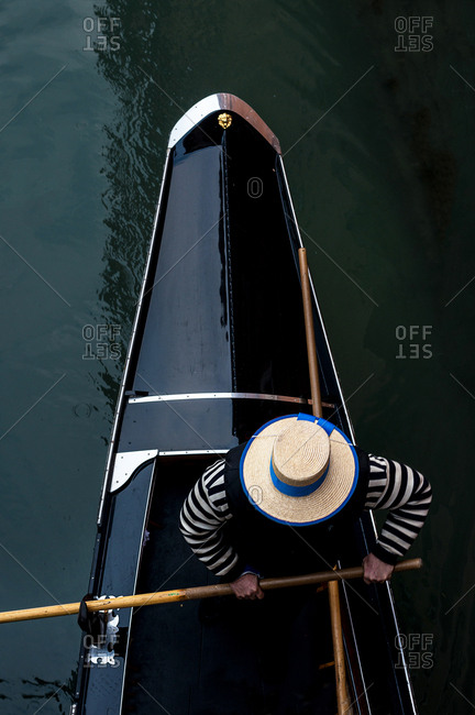 A gondolier with the typical hat rowing his boat