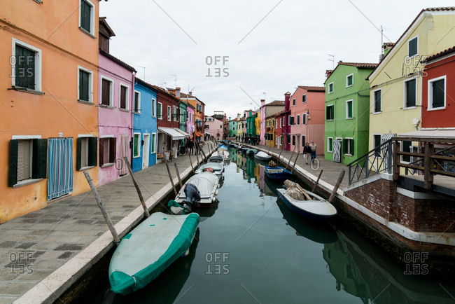 Venice, Italy - February 26, 2016: Colorful canal street in Burano on a cloudy day