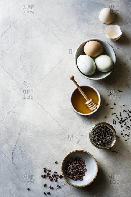 Honey, eggs, tea, cacao nibs on a light background