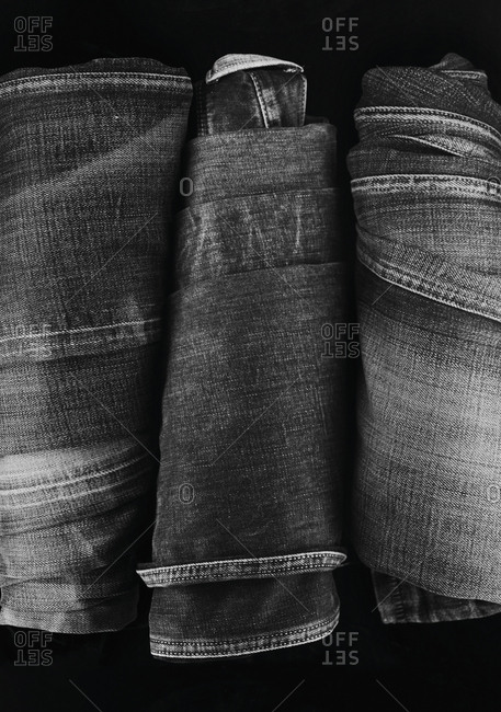 Close-up of three folded pairs of denim jeans
