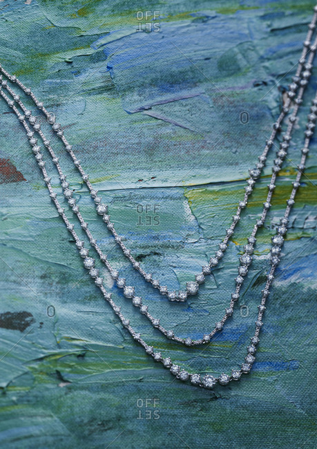 Three strand diamond necklace on painted canvas