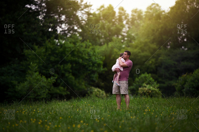 Man holding daughter in field at sunset