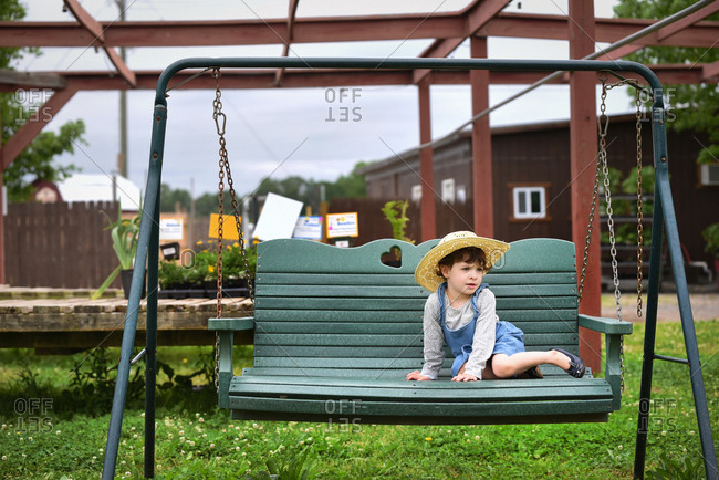 Little girl sitting on swing at farm