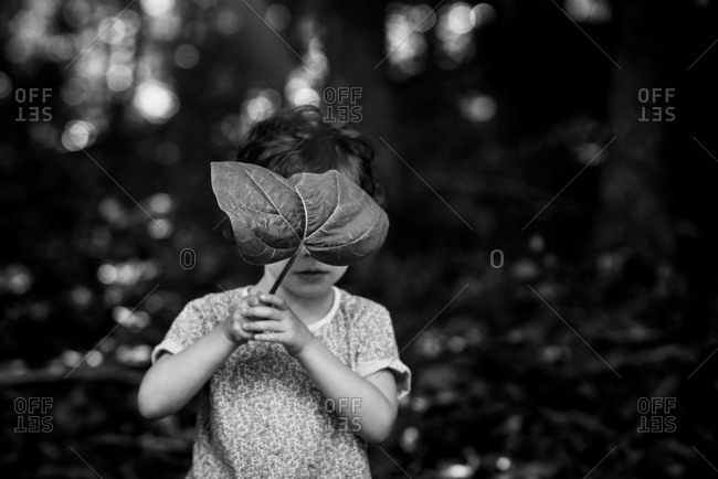 Little girl hiding behind a leaf
