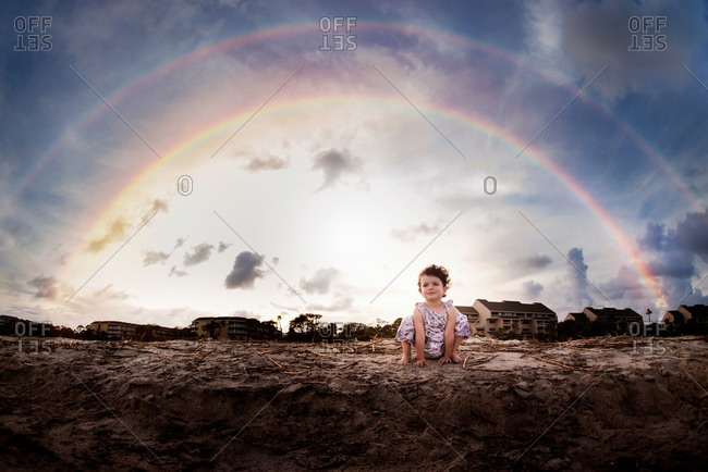 Little girl sitting on sand with rainbow in background