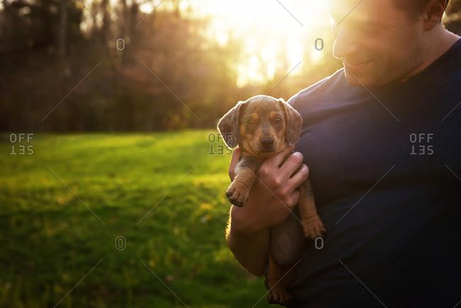 Man holding dachshund puppy at sunset