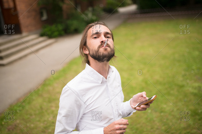 Man holding cell phone while smoking