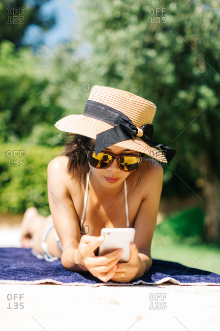 Woman by poolside using phone