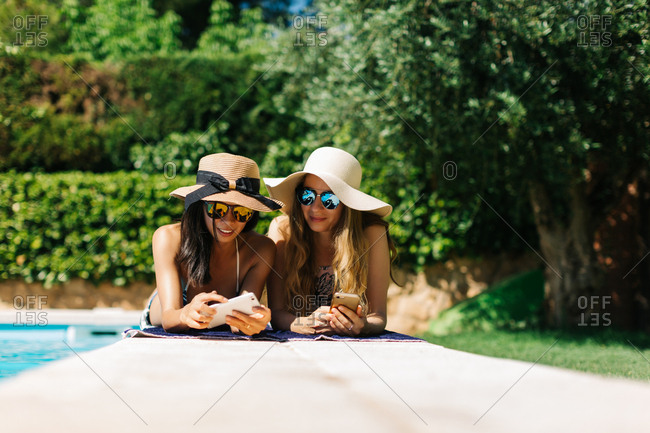 Women at poolside using phone