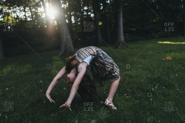 Girl doing backbend in forest setting