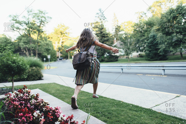 Girl in backpack jumping to sidewalk