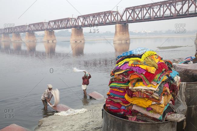 Agra, India - October 20, 2011: People washing saris in river