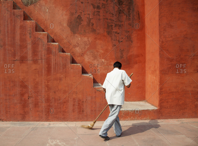 Man sweeping by stairs in India