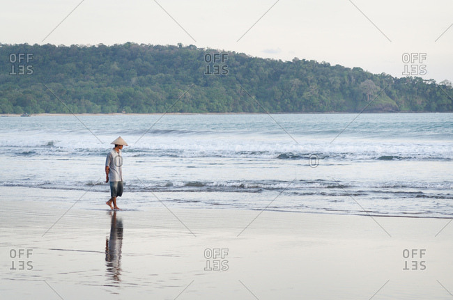 Pangandaran, Indonesia - May 22, 2011: A man wearing a woven conical rice hat strolls along the beach enjoying the calm ocean waves