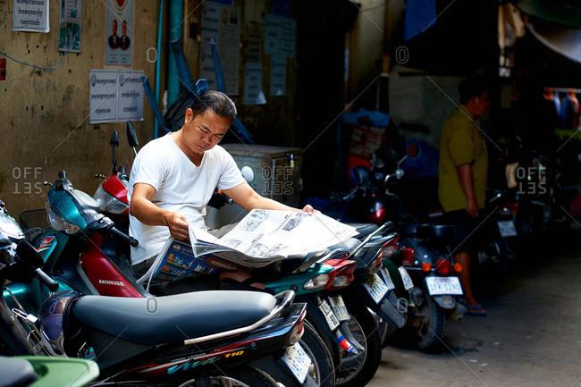Phnom Penh, Cambodia - June 24, 2017: Man reading newspaper