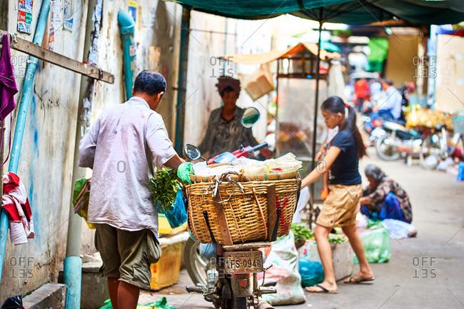 Phnom Penh, Cambodia - June 24, 2017: Man preparing vegetables for sale