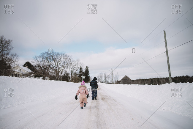 Kids walking in snowy farmland road