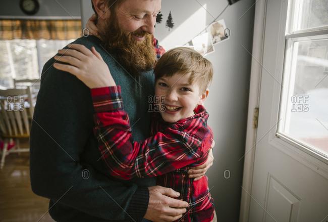 Boy in flannel hugging dad