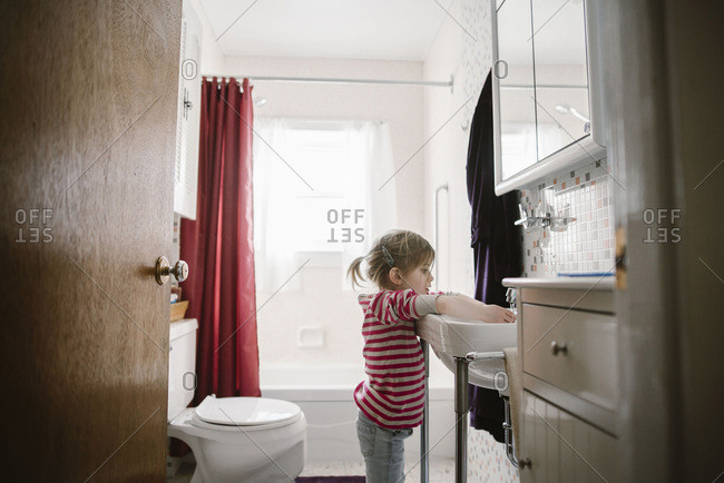 Girl washing hands in bathroom sink