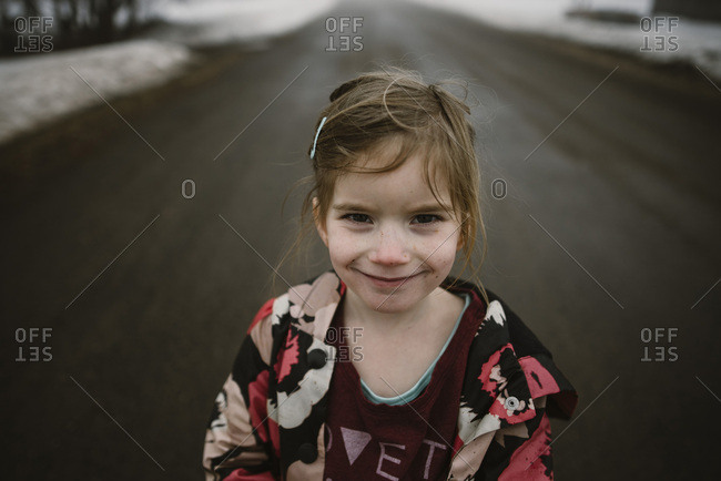Girl on a rural winter road smiling