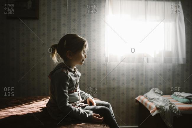 Girl sitting still in bedroom sunlight