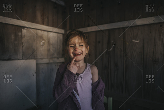Girl laughing inside a shed