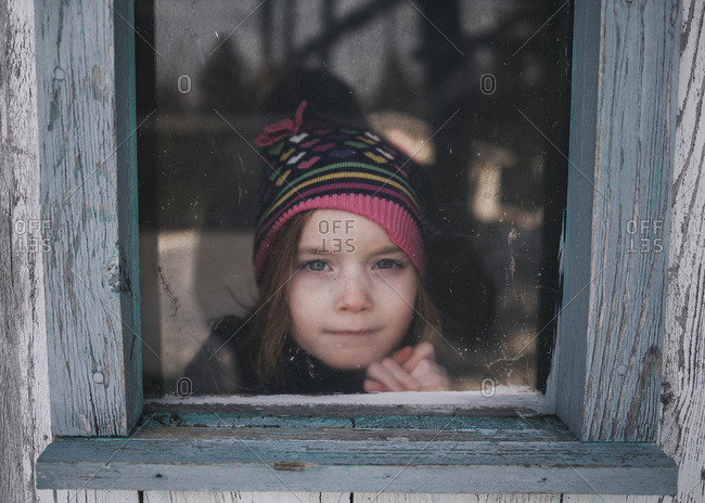 Girl looking out shed window
