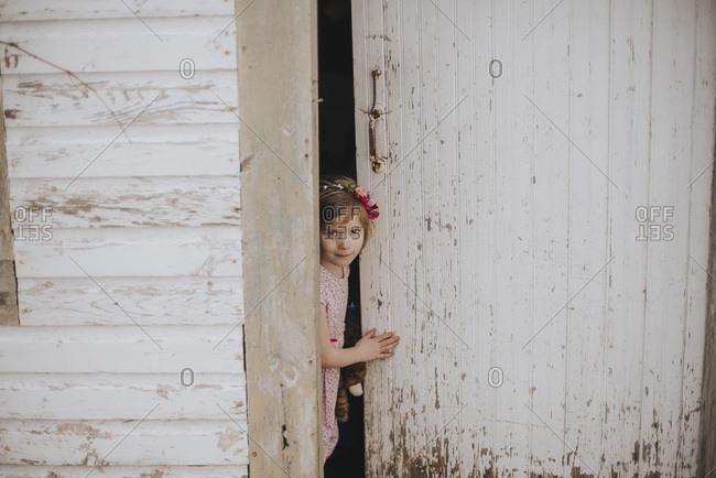 Girl peeking out a shed door