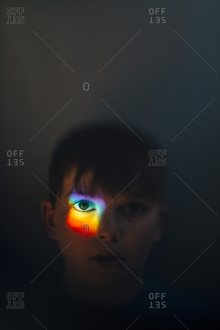 Boy with rainbow of light on eye