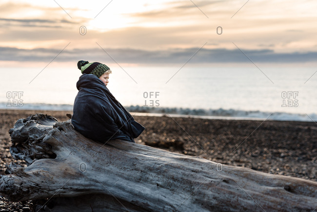 Boy in blanket on beach log