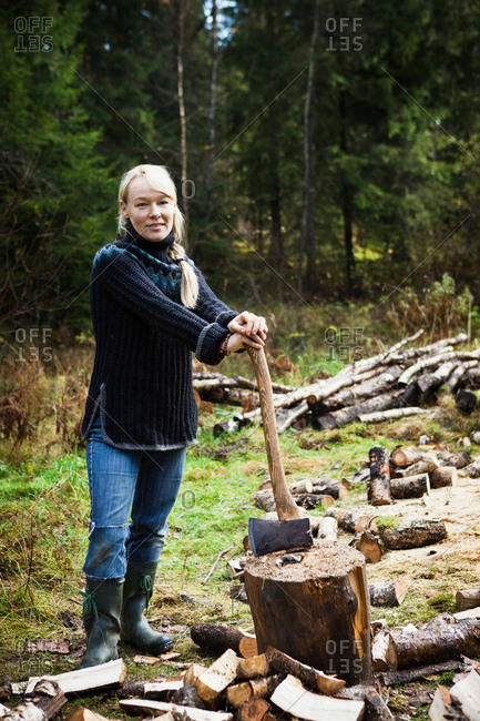 Woman chopping firewood in forest
