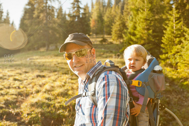 Man carrying son on back outdoors