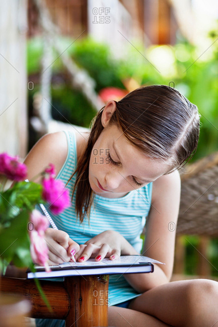 Girl writing on notebook outdoors