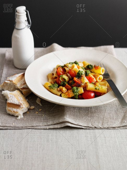 Bowl of pasta with tomatoes and bread