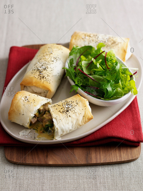 Plate of baked pastry rolls with salad