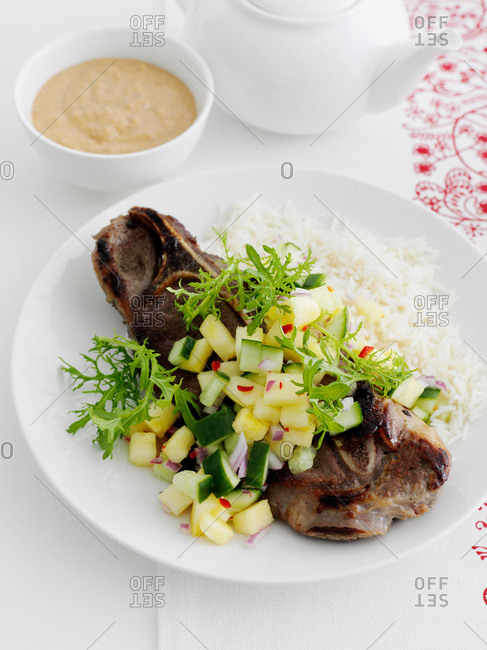 Plate of meat with chopped vegetables