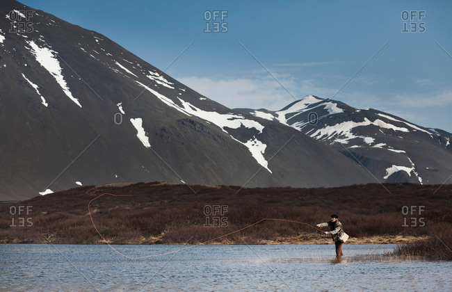 Man fishing in still lake