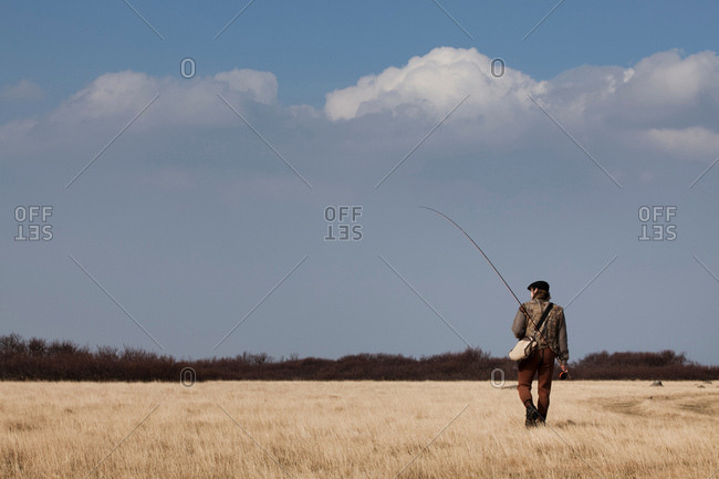 Man carrying fishing rod in grassy field