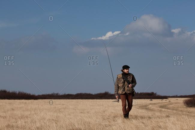 Man carrying fishing rod in grassy field