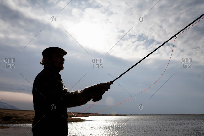 Silhouette of man fishing in still lake