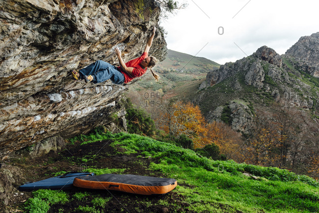 Woman rock climber  climbing overhanging boulder in scenic landscape, Asturias, Spain